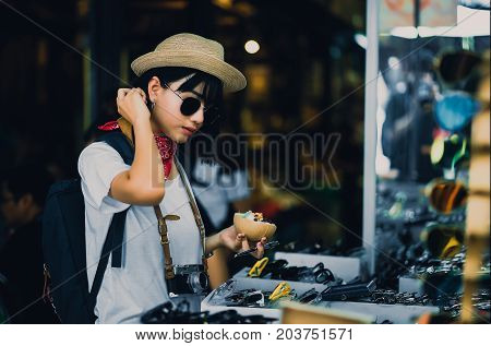 Attractive young woman who happily choose to buy sunglasses in the store happily shopping street in the city center Concept travel shopping.