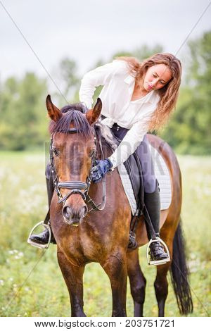 Young rider girl bent toward horse for complimenting it