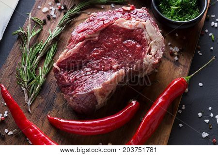 Raw rib eye steak with herbs, closeup. Cooking ingredients for restaurant dish. Fresh meat, spices and chilli on wooden desk, top view