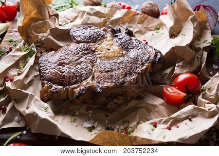 Rib eye steak on cooking paper, parchment decorated with tomato, close up