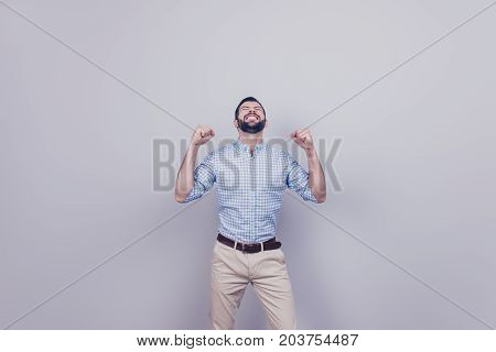 Winner! A dream of the young bearded brunet entrepreneur came true. He is very excited wearing smart outfit celebrating stands on pure background