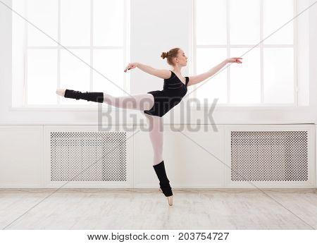 Young graceful ballerina in black at ballet class making arabesque. Classical dancer in white hall practicing positions near large window, copy space