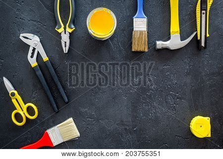 constructor desk with set of building implements and brushes on dark desk background top view mock up