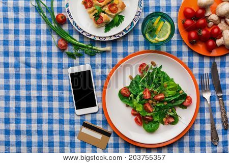 Healthy food shopping online with credit card on smartphone, copy space. Fresh salad with greens, casserole and lemonade on checkered tablecloth background. Organic vegetables top view, copy space.