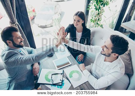 Well Done! Success And Team Work Concept. High Angle View Of Three Business Partners Are Amazed, Sit