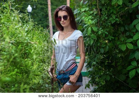 a charming young lady in mirrored sunglasses posing amid greenery in the Park