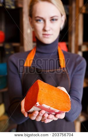 Red gouda pesto cheese. Female shop assistant suggesting colored cheese with herbs, grocery shop background