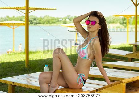 Slim sexy lady in a bathing suit and mirrored glasses posing on camera