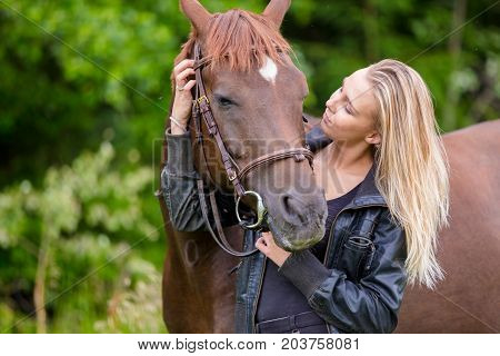 Beautiful young woman with her adult arabian horse standing in the field. Relationship between human and animal.