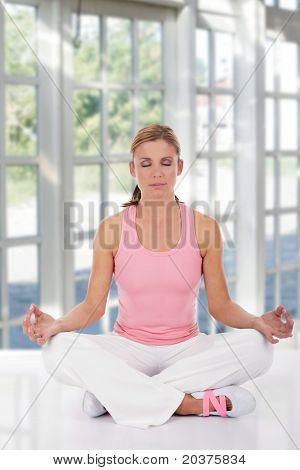 woman in fitness clothes practicing yoga at home