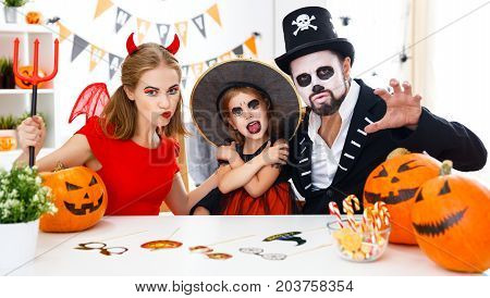 a happy family in costumes getting ready for halloween at home