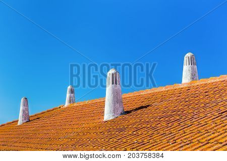 Orange roof tiles with four white chimneys and blue sky