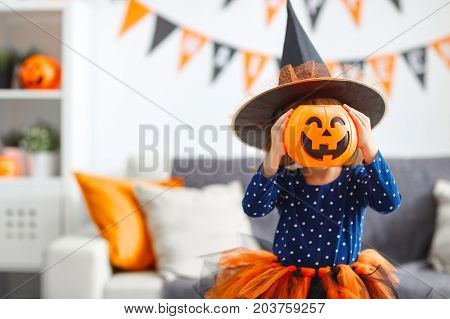 happy laughing child girl in witch costume to halloween
