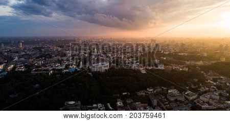 Panoramic view of a modern city at sunset. Skyline bird eye aerial view of the old part of the city under dramatic cloud sunset sky. Vladimirskaya Gorka, St. Andrew's Church, St. Michael's Golden Hills Monastery, St. Sophia Cathedral are the main sights o