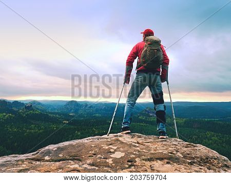 Disabled Man With Crutches Stands On A Big Rock And Looking To Mountains At Horizon.