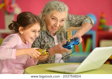 Grandmother and granddaughter playing computer games on laptop