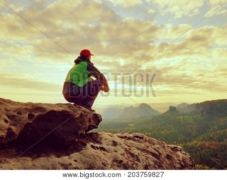 Alone Tourist Take A Rest. Hiker  In Green Black Jacket Sitting On The Rocky Peak