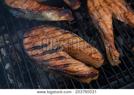 Grilled salmon red fish steaks on the flaming grill