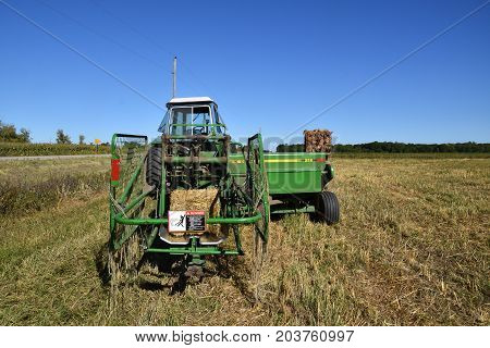 OSAKIS, MINNESOTA , September 8, 2017:  The bale thrower and tractor parked in the stubble of a wheat field are  products of John Deere Co, an American corporation that manufactures agricultural, construction, forestry machinery, diesel engines, and drive