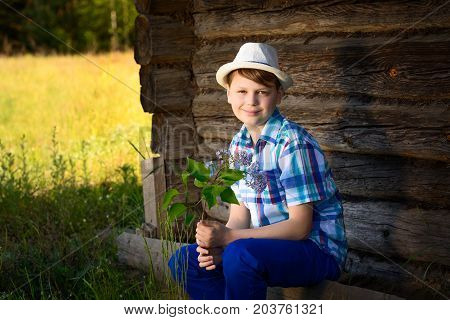 Adorable kid boy in hat smelling of lilac a bouquet of flowers in the countryside. The time of sunset, soft light, vocation and leisure concept