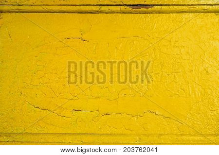 Abstract yellow solid background with cracks in the paint. Texture. A horizontal frame.