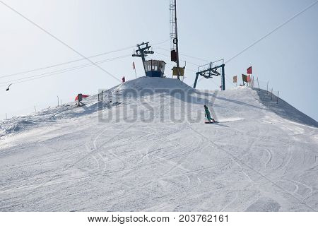 Anonymous woman snowboarding down snowy of mountain in sunlight.