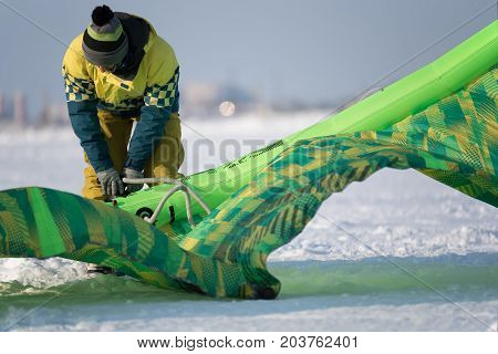 Anonymous person in warm clothing blowing up colorful kiting canvas in snowy field.