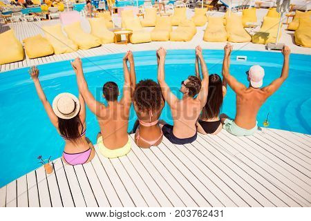 Put Your Hands Up! Pool Disco Party. Six Excited Cheerful Multi Ethnic Friends Are Chilling By The P