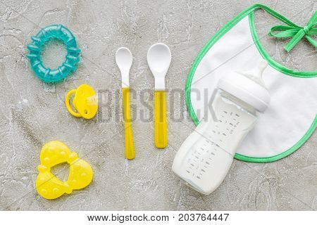 children feeding with breastmilk or infant formula powdered baby milk and toys on gray table background top view