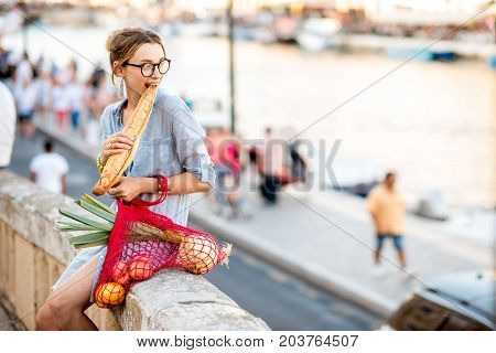 Lifestyle portrait of a young woman with mesh bag full of fresh food eating baguette oudoors in the old city
