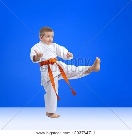 On a blue background a little athlete beats kicking