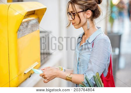 Young woman putting letter to the old yellow mailbox standing outdoors on the street
