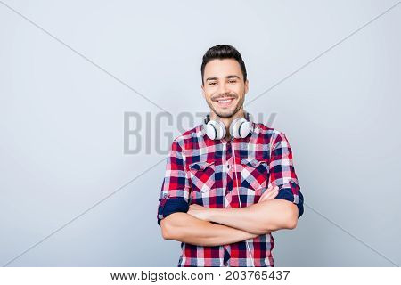 Portrait Of Cheerful Young Brunet Man In Casual Outfit, With Big White Modern Earphones, Standing Wi