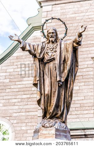 Ile D'Orleans Canada - June 1 2017: Saint-Jean church parish with stone architecture and Jesus Christ statue with outstretched open arms and illumination lamps