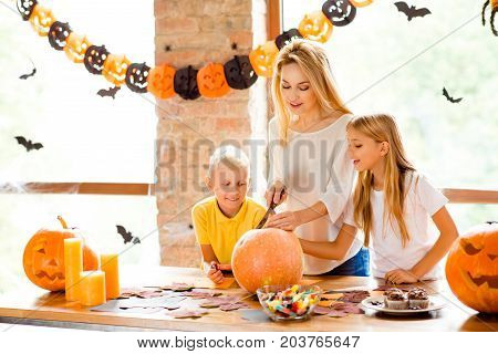 Trick Or Treet! Blonde Attractive Mum With Two Small Adorable Kids Is Preparing The Jackolantern At