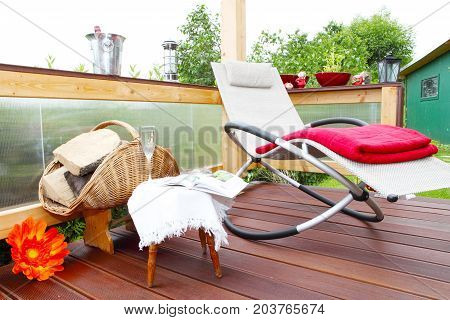 Relax Lounger with cushions and wood for the fire on the terrace