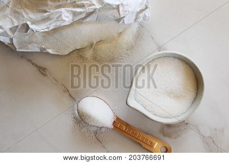 Sugar spills out of bag onto white marble with cup and teaspoon full of sugar. Copy space.