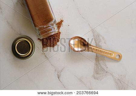Cinnamon spills out of glass jar onto white marble with copper teaspoon. Copy space.