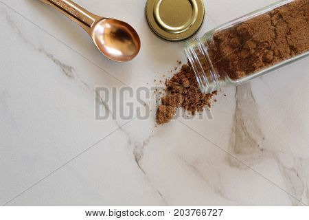 Nutmeg in a glass jar spills onto white marble with copper teaspoon. Copy space.