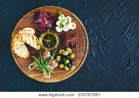 Assortment of spanish tapas or italian antipasti: Prosciutto ham bresaola Mozzarella sun-dried tomatoes olives and toasts on wooden board. Food and drink holidays concept. Top view. Copy space.