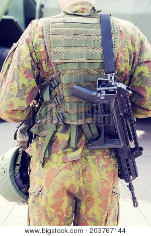 A soldier with G36 rifle in front of M113