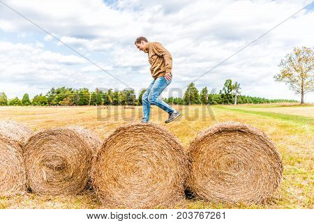 Young Man Jumping Over Hay Roll Bales In A Farm Rural Countryside Field