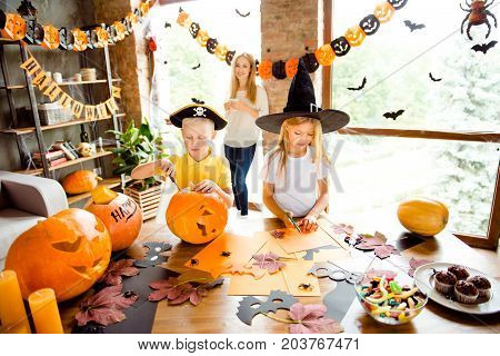 Two Busy Kids In Halloween Headwear Are Making Hand Made Decor For Party, Mum Is Watching Them From