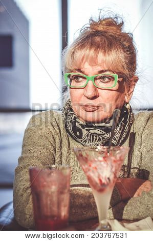 POZNAN POLAND - JANUARY 23 2017: Unidentified Polish woman with green glasses sitting at a Grycan ice cream salon table with an serious face expression