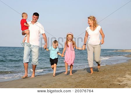 familia en las vacaciones de verano, corriendo a la playa