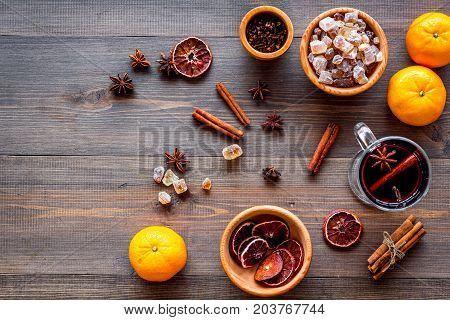 Ingredients of hot mulled wine or grog set with spices and citrus for winter evening. Christmas and new year eve. Wooden background top view.