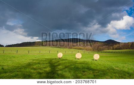 Wooden archery base mady from straws in the countryside. Beautiful spring weather with dramatic sky clouds. Green meadows with cows and horses.