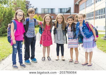 The Great Portrait Of School Pupil Outside Classroom Carrying Bags