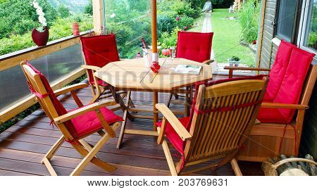 terrace with a seating of chairs and table with red cushion