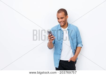 Portrait Of Young Smiling African Male Student, Typing Sms On His Phone, Wearing Casual Jeans Outfit